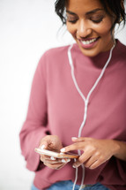 a woman listening to a cellphone with earbuds