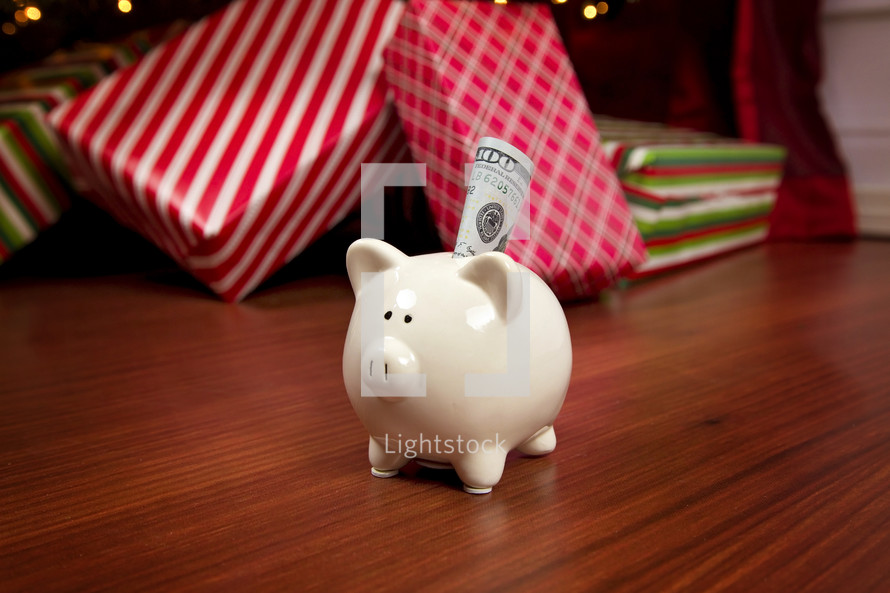 cash in a piggy bank in front of a Christmas tree