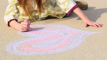a little girl drawing a Valentine's heart on concrete with sidewalk chalk