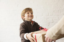 a young boy giving a wrapped gift to his mother