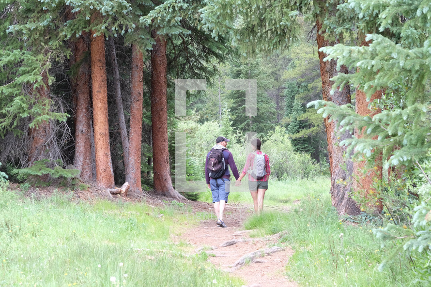 couple holding hands hiking on a trail