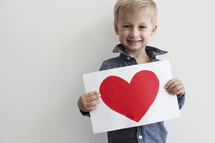 toddler boy holding a painting of a red heart