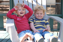 toddlers in a chair outdoors
