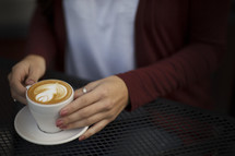 a young woman at a table with a latte