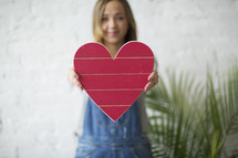 a woman in overhauls holding a red wooden heart