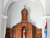 A statue of Jesus behind the altar in a Catholic church