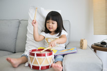 a toddler girl playing with a toy drum