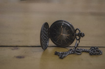 a pocket watch on a table