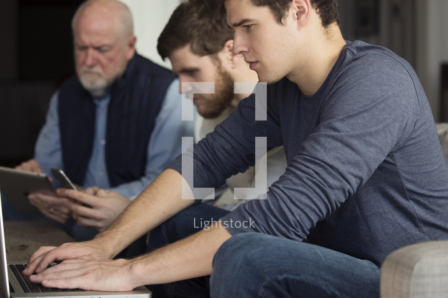 men at a meeting with cellphones and laptops.