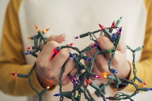 a man holding tangled Christmas lights.