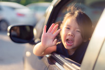 a child waving out of a car window
