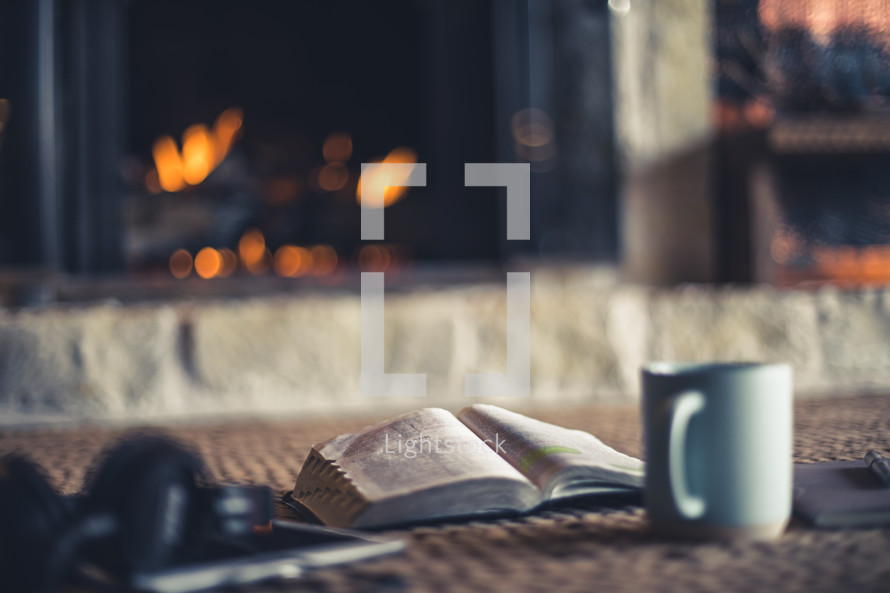 headphones, tablet, open Bible, pen, journal, and coffee cup by a fire