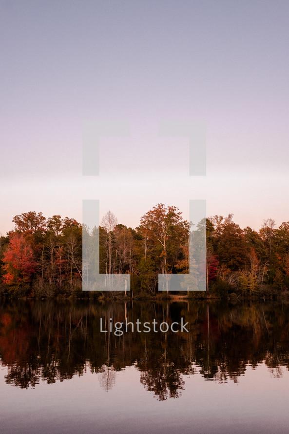fall trees reflecting on lake water