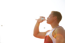 man drinking water at a sports practice