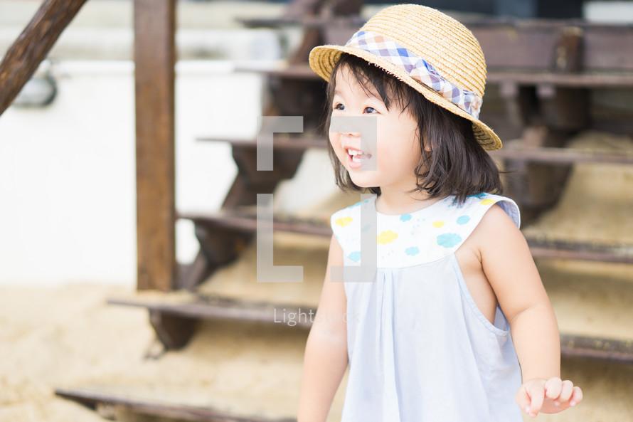happy little girl in a sunhat on a beach
