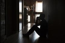a man sitting in a dark hallway praying.
