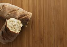 bread loaf in broken into halves on wood table top.