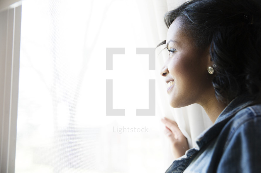 An African American woman looking out a window