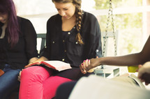 woman's group Bible study praying and discussing scripture on a porch