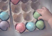 a toddler touching dyed speckled Easter eggs
