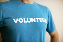 """A man wearing a blue t-shirt with the word """"volunteer"""" printed on it."""