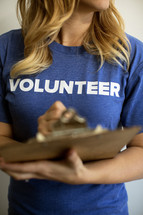 "A woman with a clipboard wearing a blue t-shirt saying, ""volunteer."""
