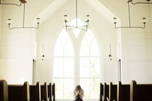 Woman praying in front of a window in a church.