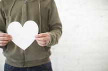 A man stands holding a white paper heart.