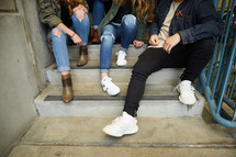 group of teens talking sitting on steps