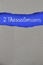 2 Thessalonians - torn open kraft paper over intense blue paper with the name of the second letter from Paul to the Thessalonians