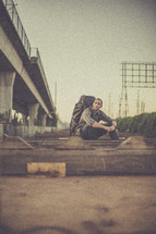 man sitting on the ground outdoors with a backpack