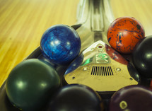 bowling balls in a ball return at a bowling alley