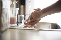 a  woman washing her hands in a sink.