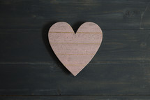 A pink heart of wood on dark wood.