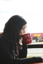 a woman sipping from a coffee mug