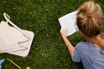 a woman lying in the grass reading a Bible.