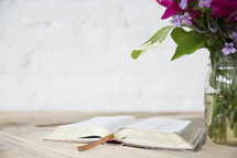 open Bible, and flowers in a vase on a wood table