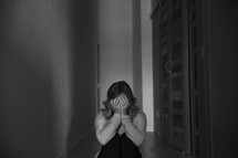 a woman sitting alone in a hallway covering her face with her hands