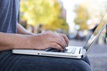 a laptop sitting on a man's lap