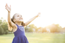 Happy, young girl standing outdoors with raised arms in praise.