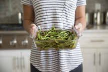 a woman holding green beans