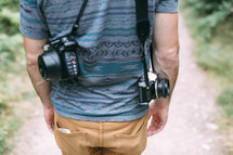 a photographer walking down a path carrying a camera