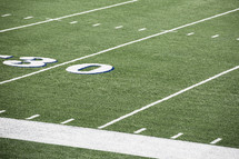 lines on a football field at the 30 yard line.