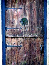 An old weather beaten wooden door framed with metal hinges. One cannot help but wonder what history this door has witnessed. I found this door to someone's home in historic Saint Augustine, Florida and just thought it had so much character and charm with its many colors and weathered exterior.