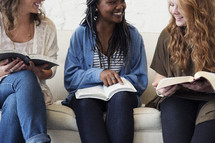 a young women sitting on a couch reading a Bibles