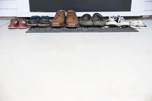 row of a families shoes in front of a door