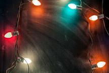 glowing Christmas lights over a chalkboard
