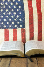 An open Bible in front of an American flag.