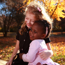 Sisters  hugging outdoors in the fall.
