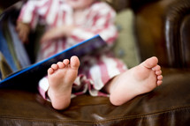 feet of a toddler boy in pjs sitting on a leather couch